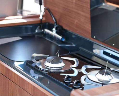 Bordküche mit Druckwasser Spüle, Gaskocher, Kühlschrank und Mikrowelle bei DONAU YACHTEN - ihr exklusives Charter-Erlebnis